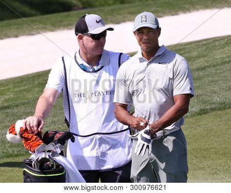 PONTE VEDRA BEACH, FL-MAR 14: Tiger Woods (R) and caddie Joe LaCava wait on the fairway during the first round of The PLAYERS Championship on The Stadium Course at TPC Sawgrass on March 14, 2019.