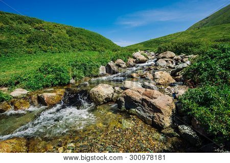 Mountain Creek With Big Boulders In Sunny Green Valley Near Hills Under Blue Sky. Clean Water Stream