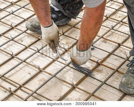 Closeup shot of bar bender hands fixing steel reinforcement bars with binding wire