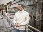 One attractive man in urban setting in modern city, leaning on metal handrail, wearing beanie cap and wool sweater, looking away poster