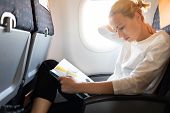 Woman feeling neck pain while reading in flight magazine on long intercontinental airplane flight. Female traveler uncomfortable seated in passenger cabin. poster