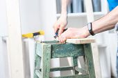 Joinery: furniture master restores the old dilapidated stool. Tearing out an old nail with nippers. poster