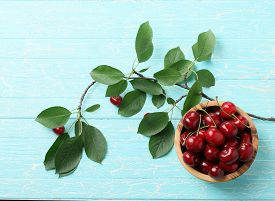 Ripe Cherries In A Wooden Bowl On The Background Of Wooden Painted Boards