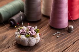 Needle Bed With Pins, Thimble And Spools Of Thread On The Background Of Wooden Boards Close-up
