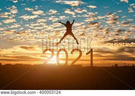 Silhouette Of Young Woman Jumping To Happy New Year 2021 In Sunset Or Sunrise Background.