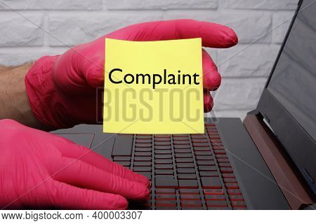 Complaint-a Word On Yellow Paper In The Hand With A Red Glove And A Hand On The Laptop Keyboard.