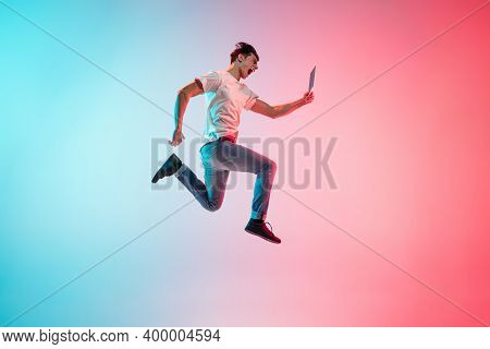 Winner With Tablet. Young Caucasian Mans Jumping On Gradient Blue-pink Studio Background In Neon Lig