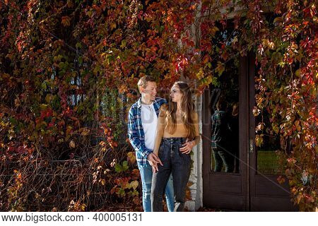Young Beautiful Couple In Love In A Good Mood Posing Against The Background Of Red Leaves Of Wild Gr
