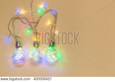 Christmas Garlands In The Form Of Light Bulbs On A Beige New Year's Composition, Christmas Concept,