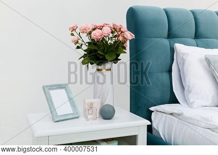 White Bedside Table Near The Bed, Against A White Wall. On The Bedside Table Are Objects, A Vase Wit