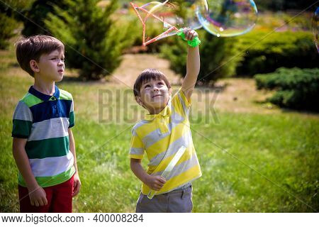 Boy Blowing Soap Bubbles While An Excited Kid Enjoys The Bubbles. Happy Teenage Boy And His Brother