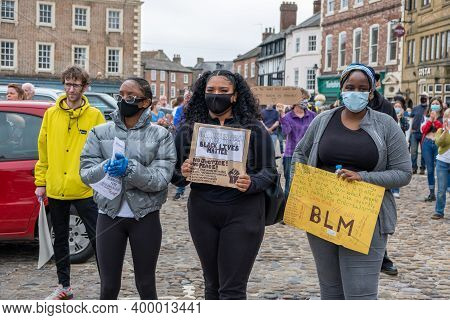 Richmond, North Yorkshire, Uk - June 14, 2020: Three Black Girls Wearing Face Masks Hold Banners At