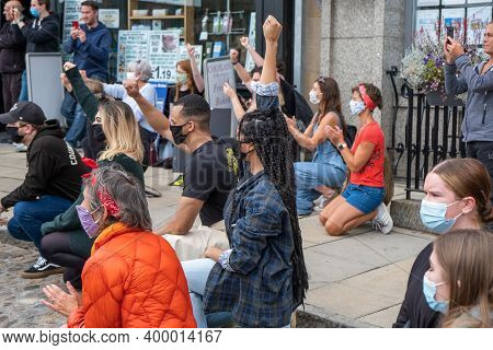 Richmond, North Yorkshire, Uk - June 14, 2020: A Strong Black Woman Holds Up Her Hand While Kneeling