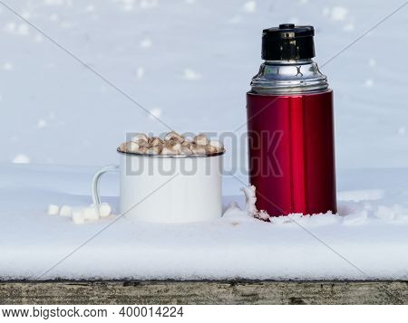 Red thermos with hot chocolate drink on table outside