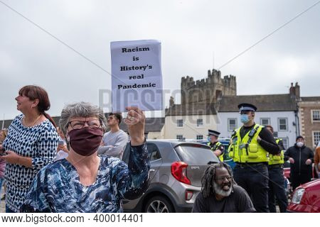 Richmond, North Yorkshire, Uk - June 14, 2020: A Woman Wearing A Face Mask Holds An Anti-racism Plac