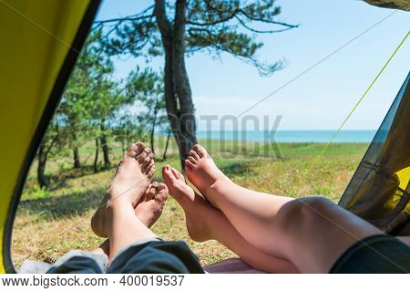 Man And Woman Are Resting In A Camping Tent, In The Foot Frame