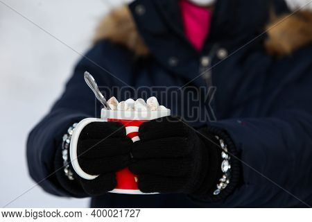 Woman is holding cup with hot chocolate beverage and marshmallows