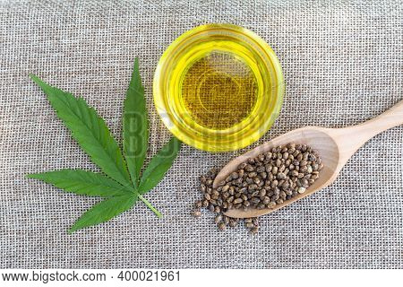 Glass Bottle With Cbd Hemp Oil, Hemp Leaves And Hemp Seeds. Research Concept Studies The Extraction