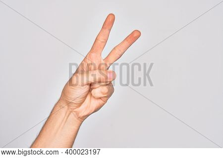 Hand of caucasian young man showing fingers over isolated white background counting number 2 showing two fingers, gesturing victory and winner symbol
