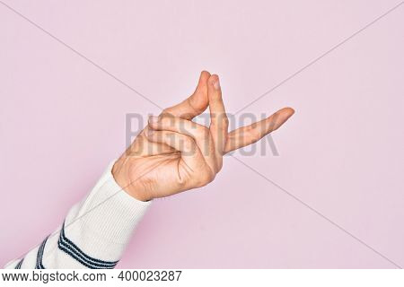 Hand of caucasian young man showing fingers over isolated pink background snapping fingers for success, easy and click symbol gesture with hand