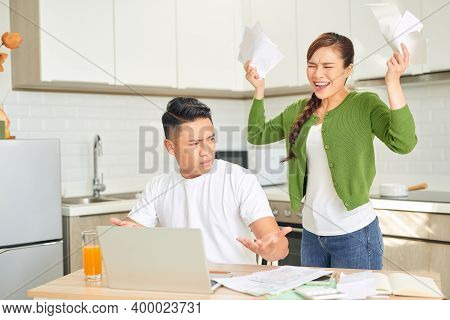 Upset Young Woman With Financial Bills Having Conflict With Man At Home