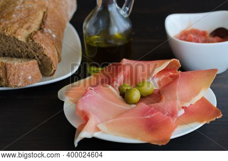 Plate With  Slices Of  Spanish Jamon Iberico( Iberian Ham), Usually Eaten With Olive Oil Or Tomato