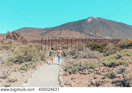 Tourists Walking In The National Park Of Las Canadas  Del Teide, Canary Islands , Spain.   Beautiful