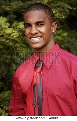 red hot business man wearing red shirt with tie. african american, attractive, and sporting earrings and braces. poster