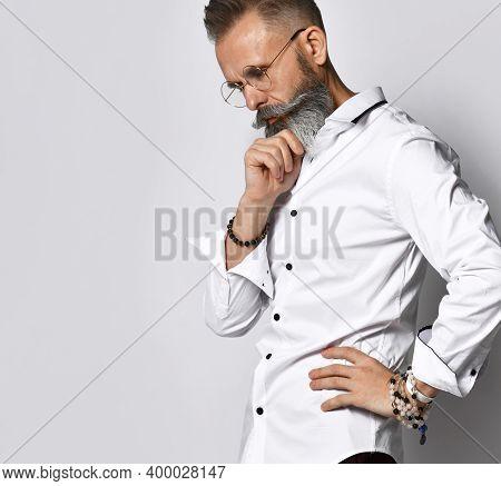 Thoughtful Pensive Stylish Bearded Hipster Man In Eyewear Stroking Touching Beard. Studio Shot Close