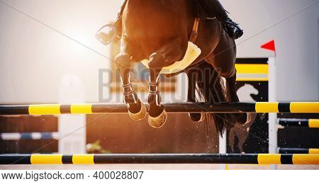 The Hooves Of A Fast Bay Horse With A Rider In The Saddle, Which Jumps Over A High Black-and-yellow