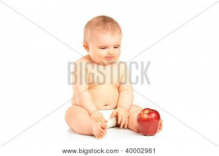 A 9 months old baby boy sitting and looking at a red apple isolated on white background