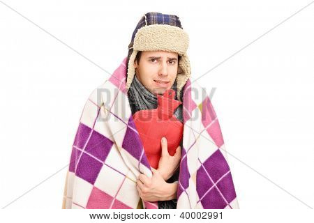 Sick man covered with blanket holding a hot-water bottle isolated against white background