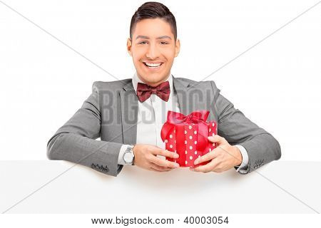A handsome guy with bow tie holding a gift behind a blank panel