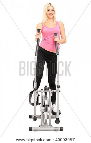 Full length portrait of a female athlete exercising on a cross trainer machine isolated on white background