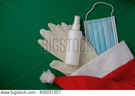 Santa Hat With Protective Mask, Gloves And Hand Sanitizer. Christmas During The Coronavirus Epidemic