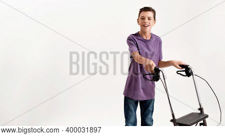 Happy Teenaged Disabled Boy With Cerebral Palsy Smiling At Camera, Taking Steps With His Walker Isol