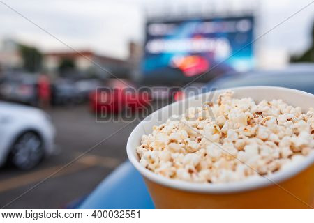 Selective Focus On Yellow Bucket Full Of Popcorn On Car Parking At Drive-in Cinema Background. Free