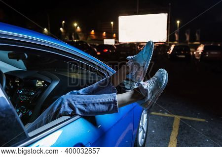 Close Up Of Woman Hanging Her Legs Out Of Car Window While Watching A Movie At Drive In Cinema From