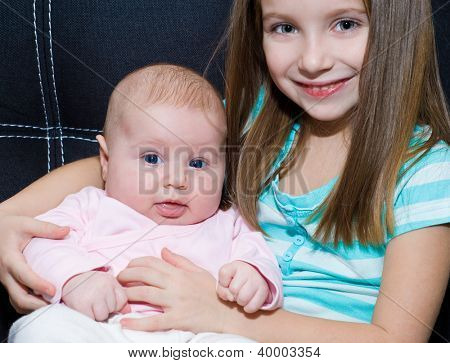 little girl and her newborn sister at home