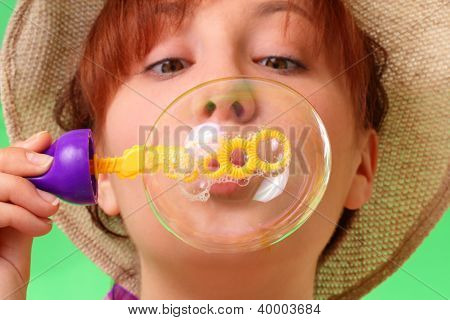 Careless Young Girl In A Hat Blowing Soap Bubbles
