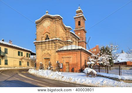 Old brick church near road through small town and snow on roadside in Piedmont, Northern Italy.