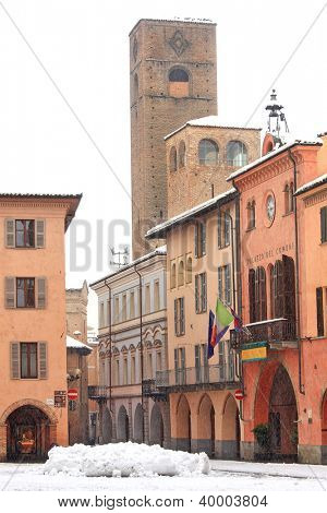 Vertical oriented image of central square, city hall and ancient tower under the snow in Alba, Northern Italy.