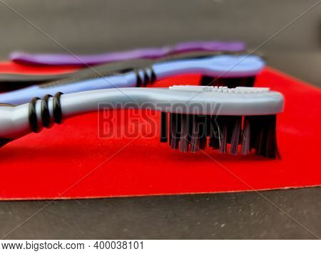 Turn Around Of Grey Tooth Brush With Black Bristle On Red Background