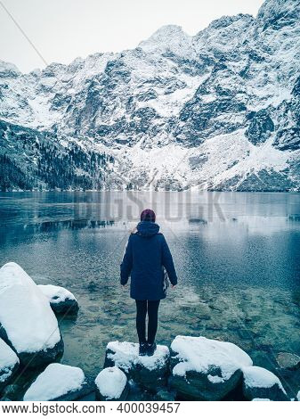 Girl Is Standing On The Shore Of A Winter Lake And Mountains Covered With Snow
