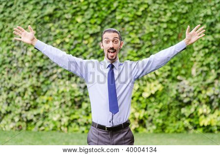 Happy businessman in the forest