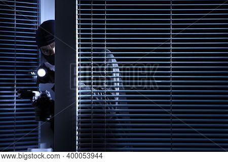 Burglary And Robbery. Skillful Professional Masked Burglar Wears A Balaclava, Holding A Gun And Torc