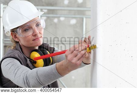 Woman Construction Worker Work With Meter Tape And Pencil, Measure Wall In Interior Building Site, W