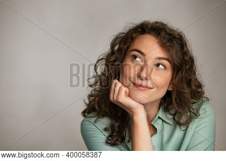 Portrait of young thoughtful woman with hand on chin having an idea against grey background. Pensive woman looking away while thinking. Close up face of girl planning her future isolated on gray wall.