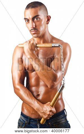 Man in martial arts concept with nunchucks