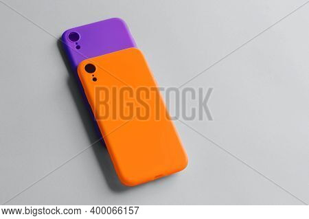 Two Silicone Cases For The Smartphone Lie On A Gray Background. Orange And Lilac Covers For The Smar